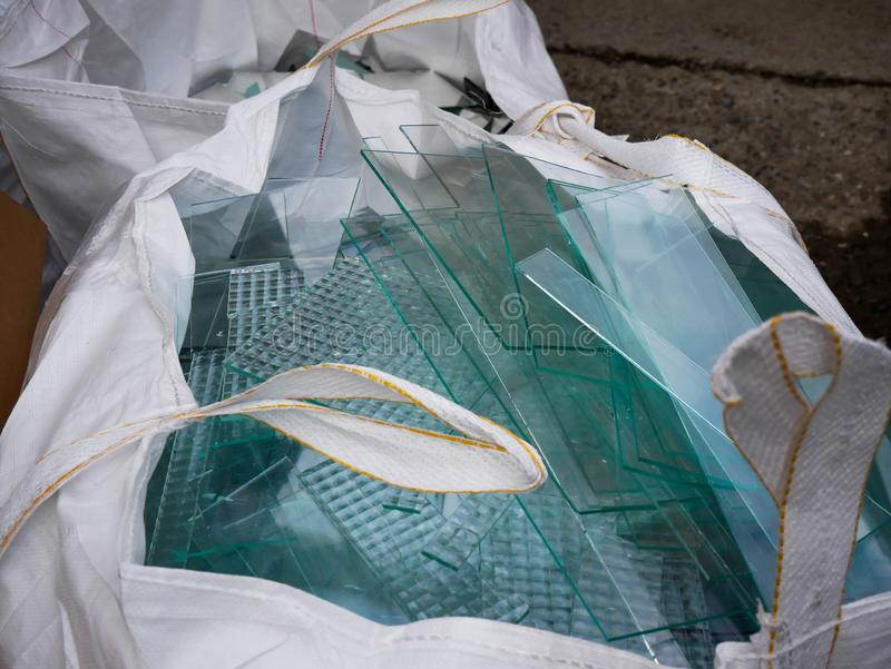 Sheet glass waste in big white plastic bags stock images