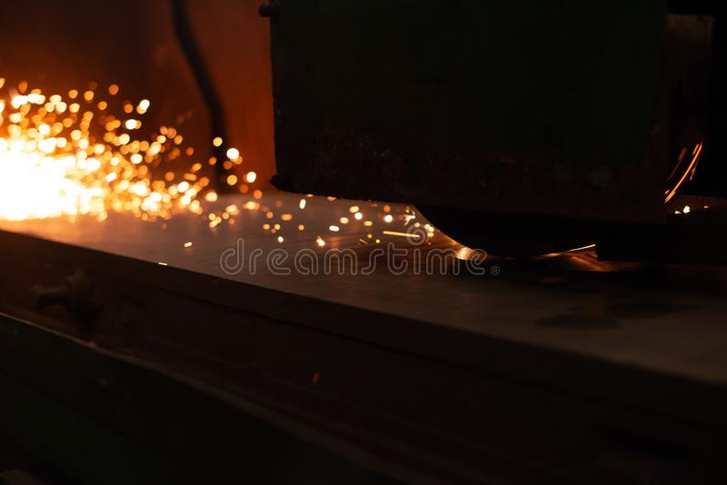 Sheet metal plate with sparking light. CNC Laser cutting of metal, modern industrial technology. Manufacturing finished parts stock photo