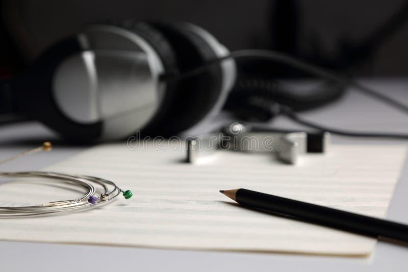 Sheet music, pencil, strings and headphones stock photos