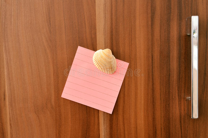 Sheet from note pad. Of the rose colour on door of the closet royalty free stock photo