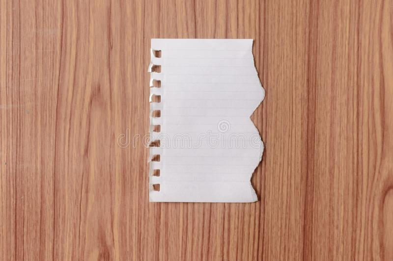 Sheet of notebook paper with torn edge blank ripped piece on isolated over wooden table background. Empty Damaged Rip Paper Shape stock images