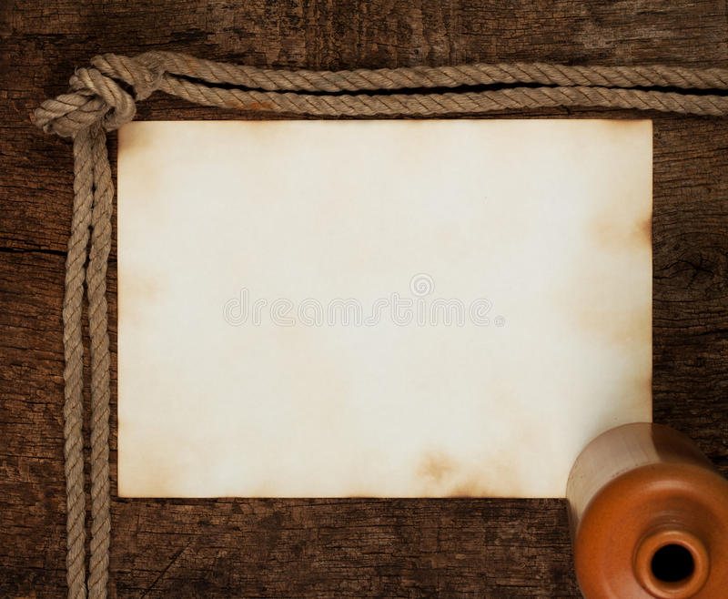 Sheet of old paper with a bottle. On a wooden background stock images