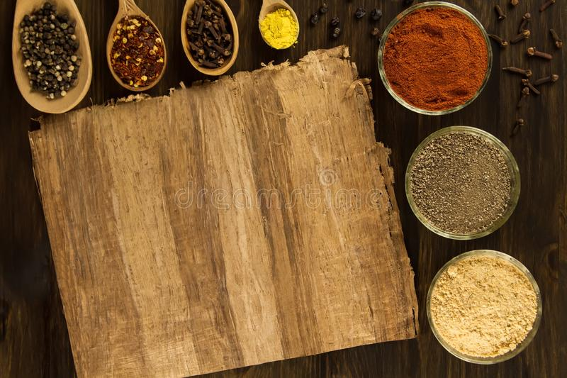 Sheet old vintage paper with spices on wooden background. Healthy vegetarian food. stock photo