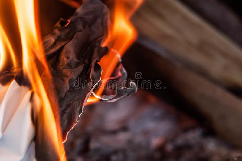 A sheet of paper burning with a red orange bright flame with heat royalty free stock photo