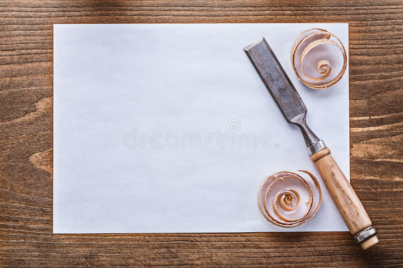 Sheet of paper curled shavings flat chisels. Construction concept royalty free stock image