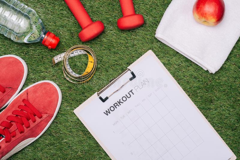 Sheet of paper and sports equipment on grass close-up royalty free stock photos