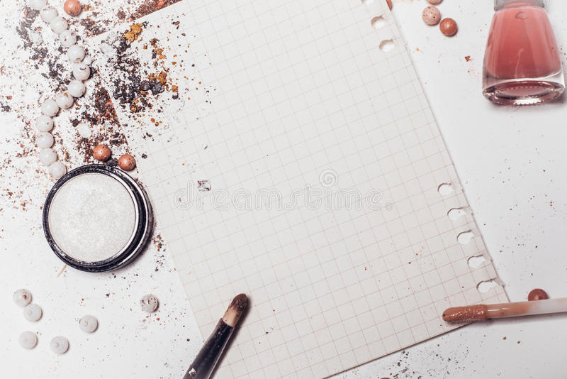 A sheet of paper surrounded by shadows, an applicator and nail polish. Abstraction. Place for inscription. A sheet of paper surrounded by shadows, an applicator stock photo