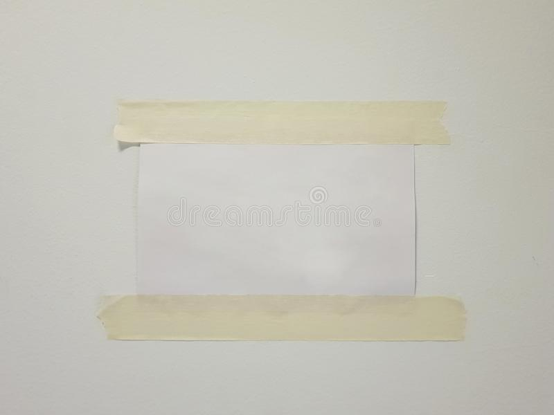 sheet of paper taped to the wall stock images