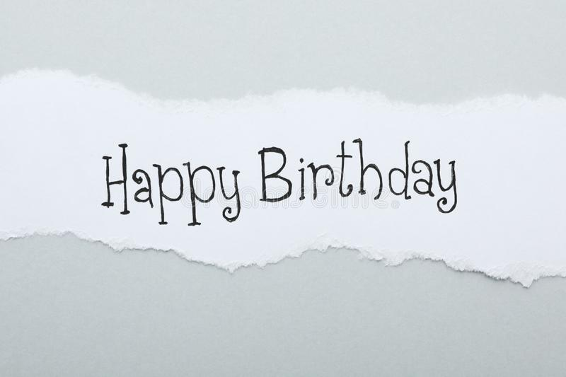 Sheet of paper with words HAPPY BIRTHDAY on light grey background royalty free stock image