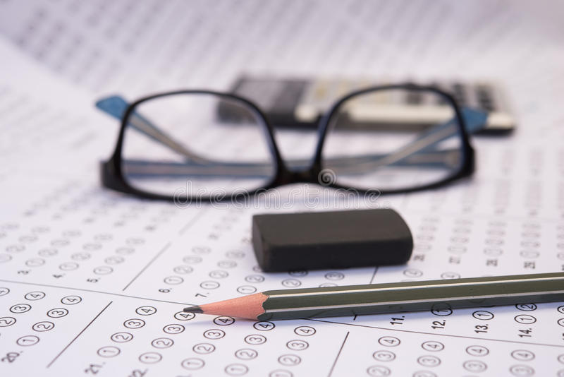 Sheet. Standardized test form with answers bubbled in and a pencil, focus on anser sheet stock photo