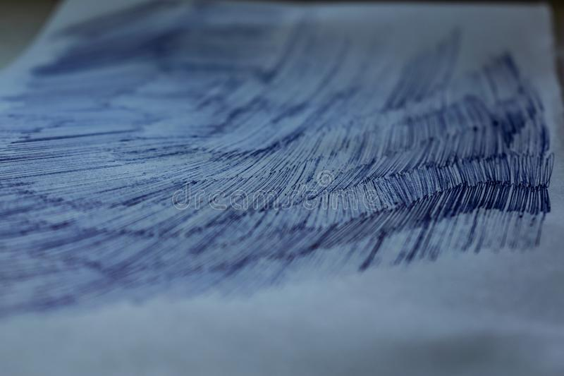 A sheet of white paper with painted dirty strokes, a blue ballpoint pen. Blurred background, shallow depth of field. Drawn record. Incomprehensible scribbles stock images