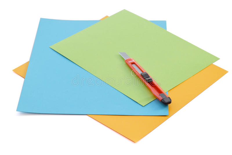 Sheets of colored paper and small stationery knife. stock photos