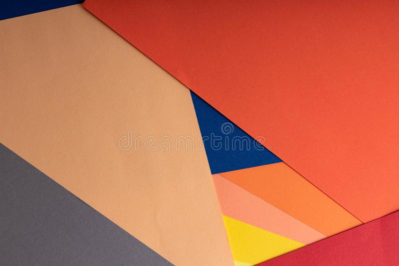 Sheets of colored paper are on the table. Paper of blue, yellow, green, blue, red, coral and peach colors. Abstract creative stock images