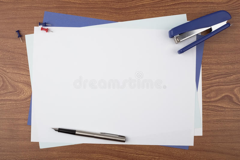 Sheets of paper and office accessories on wooden texture. Sheets of paper, a stapler, push pins, and a fountain pen on wooden texture imitating a office desk stock image