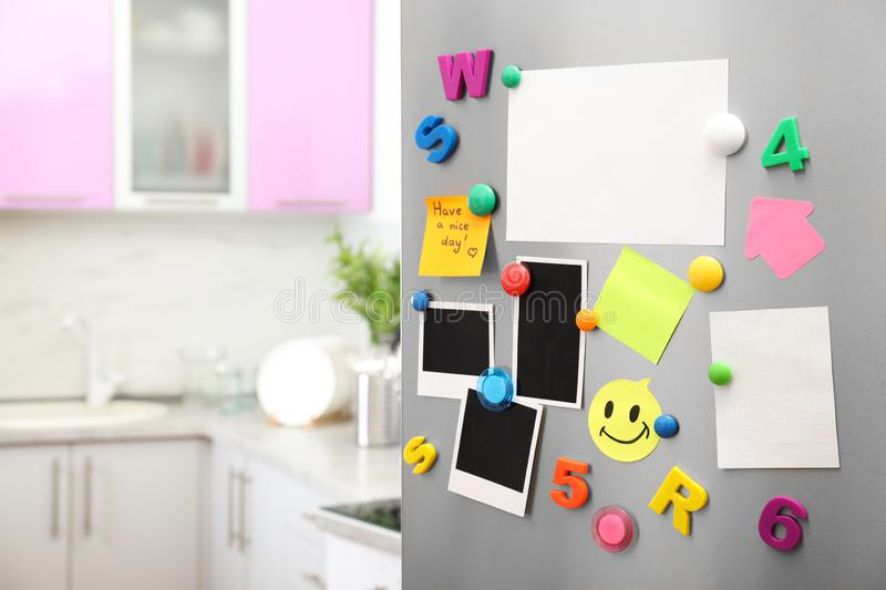 Sheets of paper and photos with colorful magnets on refrigerator door in kitchen. Space for text stock images