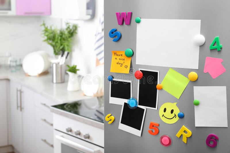 Sheets of paper and photos with colorful magnets on refrigerator door in kitchen. Space for text royalty free stock photos