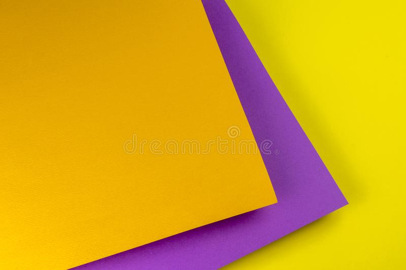 Sheets of paper placed one above the other. Background of yellow, orange and purple paper royalty free stock images