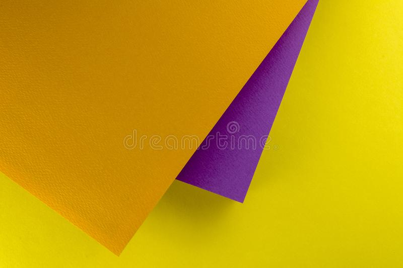 Sheets of paper placed one above the other. Background of yellow, orange and purple paper royalty free stock photography