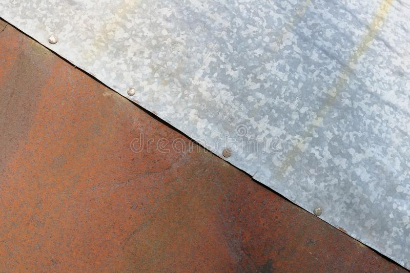 Sheets of rusty red and estimated silver steel are riveted together royalty free stock photos
