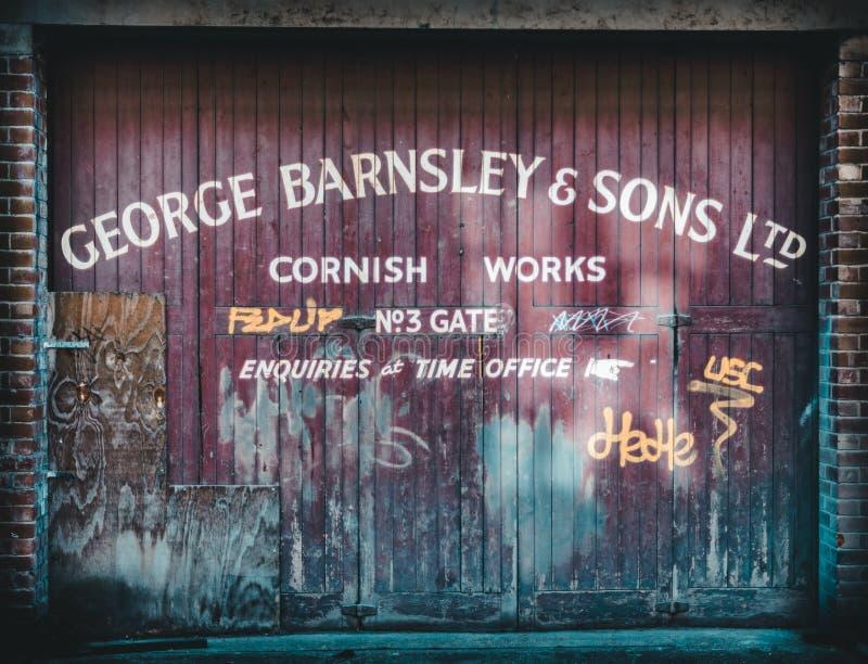 SHEFFIELD, INGLATERRA - 13 DE OCTUBRE DE 2018: Una muestra para una compañía en una puerta de madera roja del garaje en Sheffield imagen de archivo