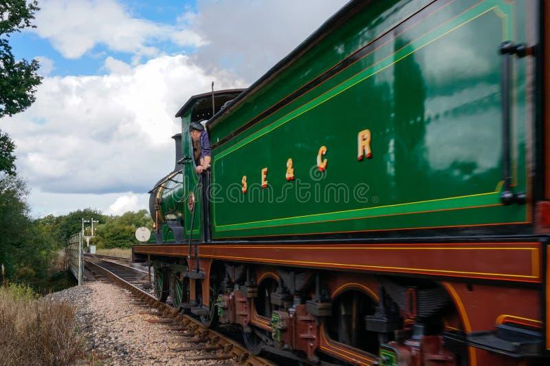 SHEFFIELD PARK, EAST SUSSEX/UK - SEPTEMBER 8 : C Class steam eng. Ine leaving Sheffield Park station East Sussex on September 8, 2013. Unidentified man stock image