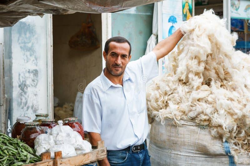 SHEKI, АЗЕРБАЙДЖАН - 20-ое июля 2015: портрет шерстей мужской овцы продавца смотря камеру стоковое изображение