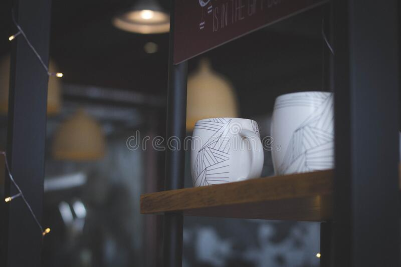 Shelf with coffee cups royalty free stock photos