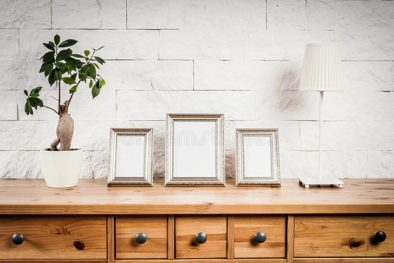 Shelf with frames and flower. Wooden shelf with frames and flower against a brick wall royalty free stock photo