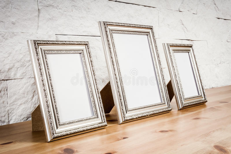 Shelf with frames and white wall. Wooden shelf with frames and white wall with bricks royalty free stock photo