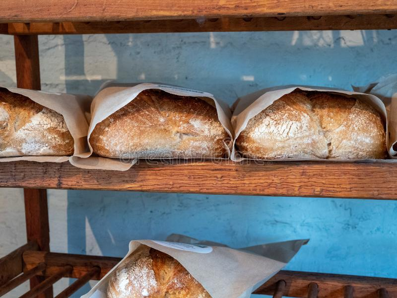 Shelf holding rows of baked and packaged loaves of bread in a bakery stock images