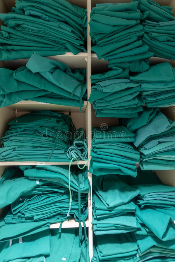 A shelf with surgical laundry. A shelf with green coloured surgical laundry in various sizes royalty free stock photography