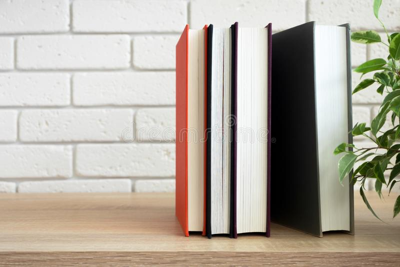 Vertical standing group of books on modern shelf in front of white wall stock photo