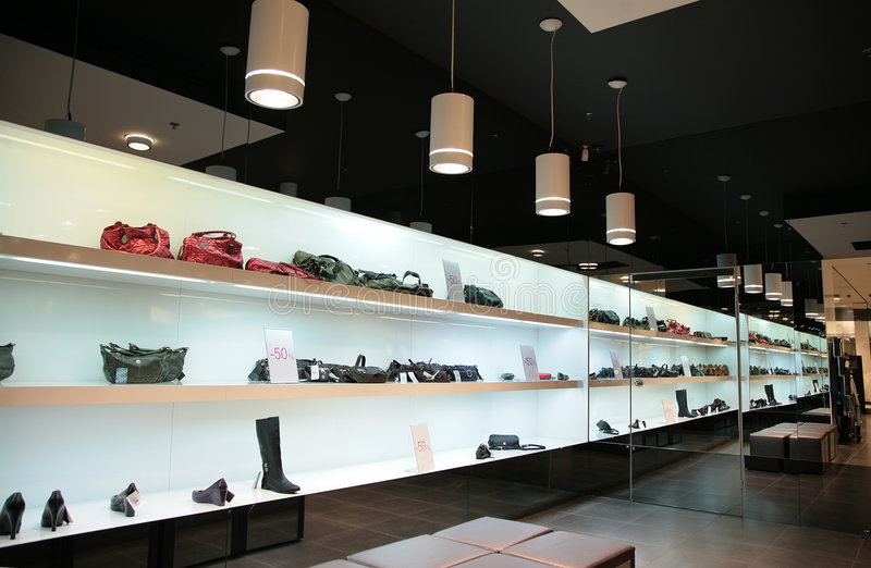 Shelfs in store with bags and shoes stock images
