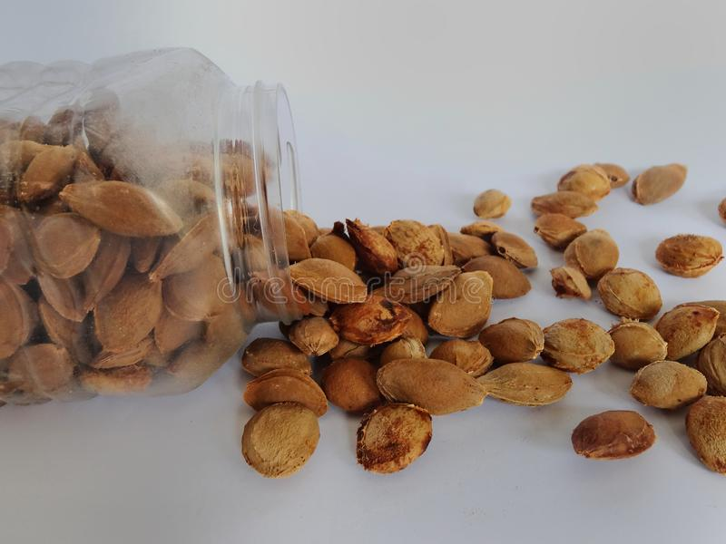Shell almonds drops from plastic jar. Shells of almonds drop off from the jar of plastic. Some shell almonds are inside of the jar and some are outside of the stock photo