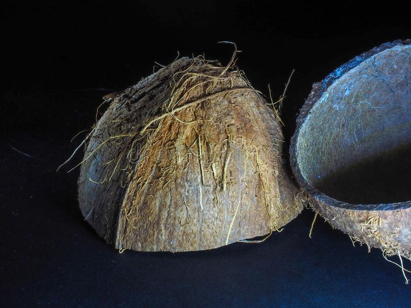 The shell of the chopped coconut dried and having an interesting structure lies on a dark background stock photography