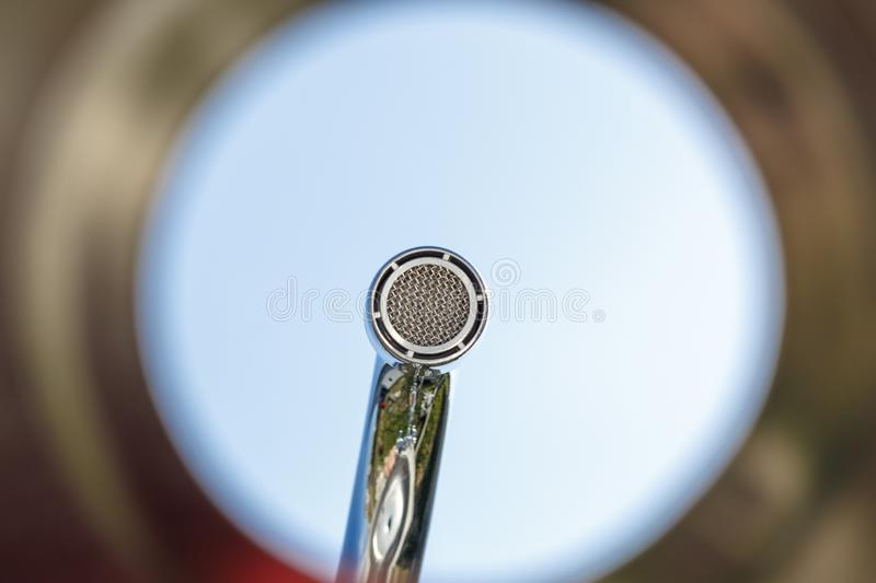 Shell, colorful, bottom view. faucet aerator, close up. background blue sky. Shell, colorful, bottom view. faucet aerator, close up background blue sky equipment stock image