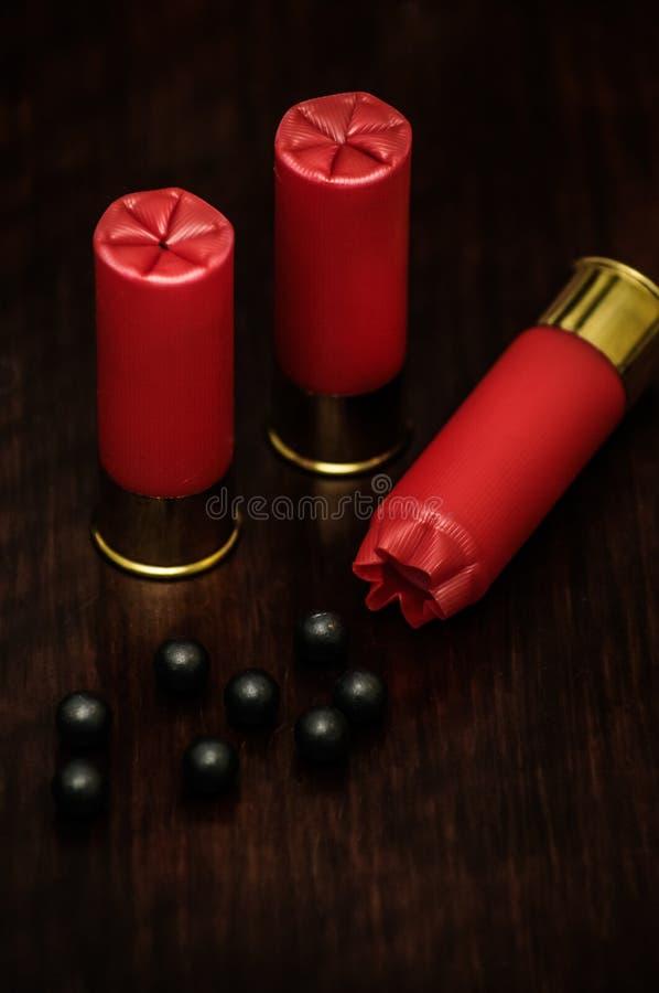 Shell de espingarda vermelhos em uma superfície de madeira imagem de stock