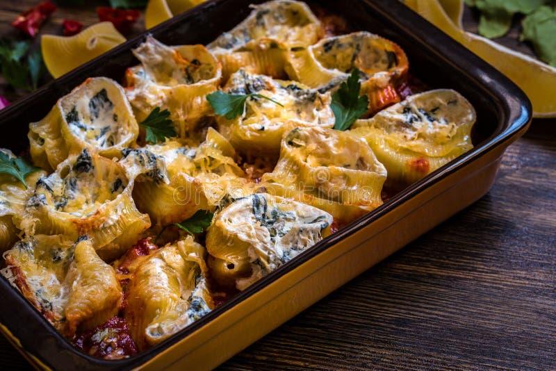 Shell-deegwaren met spinazie, roomkaas, Parmezaanse kaas in tomatensaus worden gevuld die stock fotografie