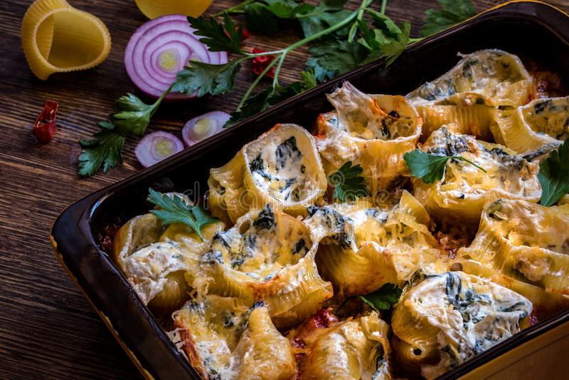 Shell-deegwaren met spinazie, roomkaas, Parmezaanse kaas in tomatensaus worden gevuld die stock foto's