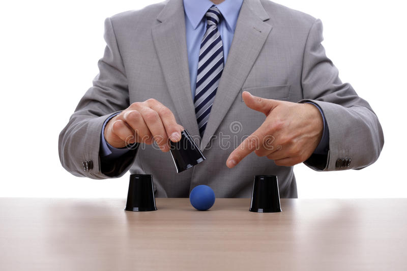 Shell game. Cup and ball guessing game success with businessman hand revealing the correct cup stock photography