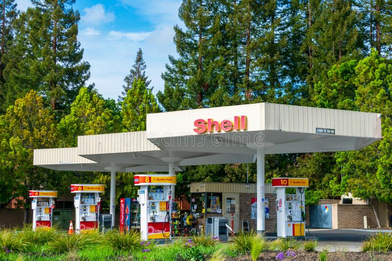 Shell gas station exterior with beautiful green landscape. Shell gas station exterior surrounded by beautiful green landscape with mature trees - Mountain View royalty free stock photos