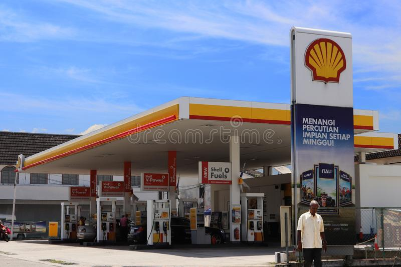 Shell Petrol Station In Malaysia. An elderly Indian man walking pass a Shell gasoline petrol station at mid-day in the suburbs of Ipoh town, Malaysia stock photo