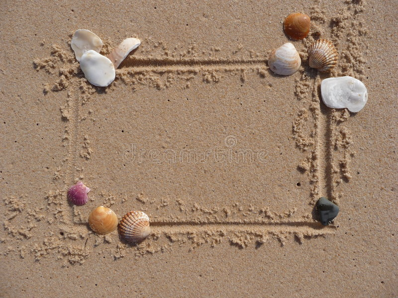 Shell and sand frame border. A frame drawn in the sand, and border decorated with beautiful sea shells royalty free stock photo