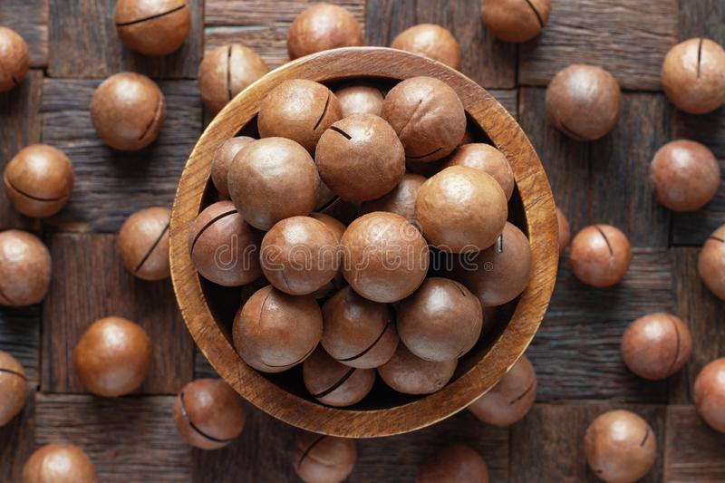 Shelled macadamia nuts in wooden bowl, top view stock image