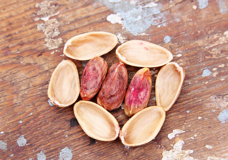 Shelled pistachio nuts. On wooden background stock image
