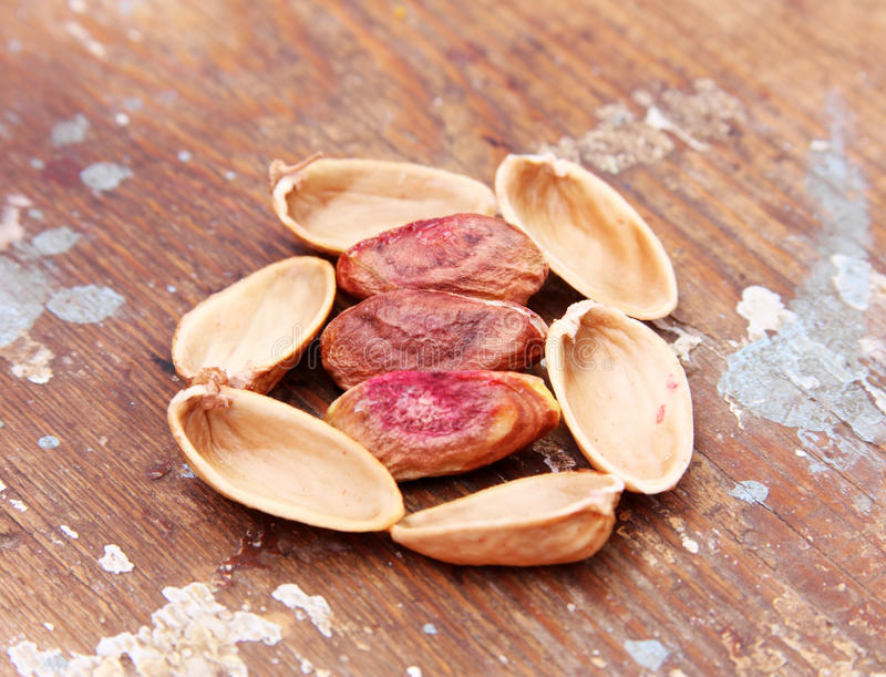 Shelled pistachio nuts. On wooden background stock photo