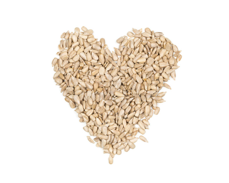 Shelled sunflower seeds heart shaped heap on white royalty free stock images