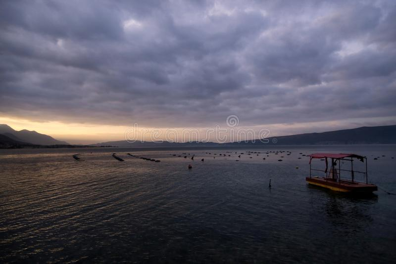 Shellfish breeding on Mediterranean sea. Mussel farm with boat on Adriatic coast. Oyster beds at low tide in oyster farm. Shellfish breeding on Mediterranean stock images