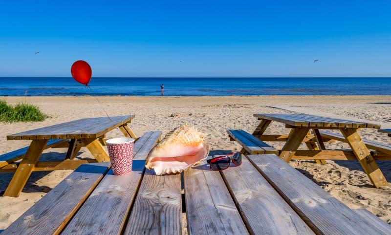 Shellfish, okulary przeciwsłoneczni, szkło z wodną i czerwoną piłką na drewnianym stole, obrazy royalty free