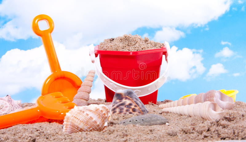 Shells and plastic beach toys. Against a blue sky royalty free stock photography